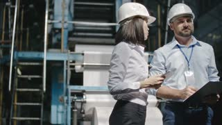 Female engineer in hard hat standing in factory workshop holding tablet and explaining something to male colleague with clipboard