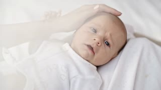 Female hand stroking head of infant baby boy lying on mothers laps and looking at camera with curiosity