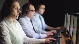 Female operator consulting clients online with male colleagues on background