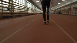 Follow shot of amputee athlete with prosthetic limb running on track inside of stadium