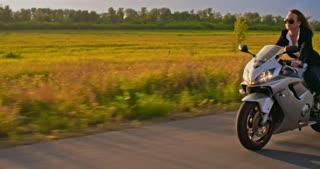 Follow shot of businesswoman riding her motorbike