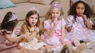 Four beautiful little girls in fancy dresses and tiaras sitting on the floor and applying lipstick