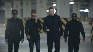 Four brutal men in black suits and sunglasses walking towards the camera in slow motion; one of them talking on the phone