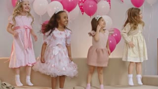 Four carefree little girls dressed like little princesses jumping on sofa together in the living room at birthday party, smiling and waving