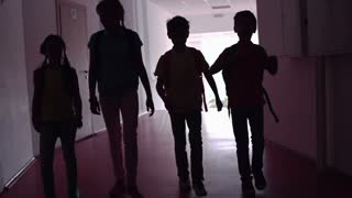 Four classmates chatting while walking along dark school corridor in slow motion