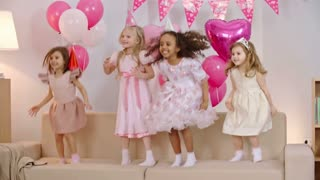 Four excited little girls with party hats on their heads jumping on sofa together in the living room decorated for birthday party with pink balloons