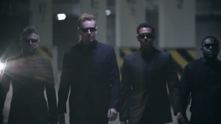 Four gangsters in black suits and sunglasses walking towards the camera in slow motion