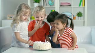 Four kids eating birthday cake with their hands