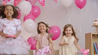 Four little girls dressed like princesses jumping on sofa and holding gift boxes at birthday party in slow motion