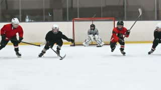 Four little hockey players skating towards the camera; boy in red uniform trying to get the puck from his opponent but falling down on ice