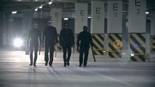 Four men dressed like gangsters walking together with baseball bats