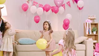 Four playful little girls dressed like princesses tossing yellow balloons in the air at birthday party
