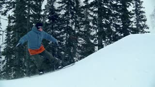 Freerider reaching mountain peak and turning snowboard back down in slow motion