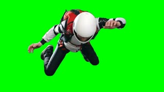 Front view Locked down slow motion shot of skydiving man performing free fall in full parachuting gear, jumpsuit, helmet and harness, against green background, extreme sports chroma key