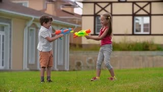 Funny boy and girl shooting water from water gun on each other in slow motion and laughing