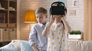 Girl in virtual reality headset looking around in the living room while little boy standing with her