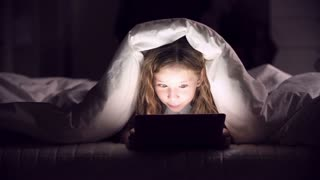 Girl wrapped in blanket on bed playing tab