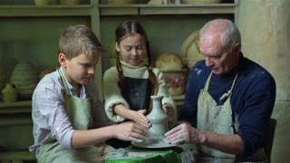 Granddad and grandchildren enjoying their family hobby, pottery