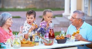 Grandparents and little grandchildren having an outdoor dinner together