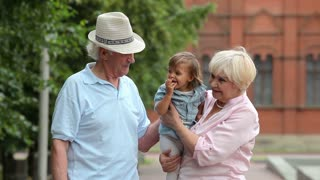 Grandparents having fun babysitting their cute granddaughter