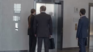 Group of business people waiting for elevator on the first floor, entering it and moving up