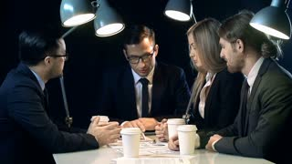 Group of four businesspeople in formalwear sitting at table in dark lamp-lit office, discussing ideas, business issues and drinking coffee over papers with graphs and charts, looking confused
