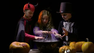 Group of kids in Halloween costumes preparing magic potion