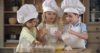 Group of lovely children pouring flour into egg mixture