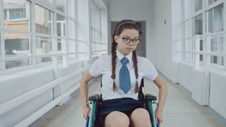 Handheld dolly-like shot of lonely and sad looking handicapped schoolgirl in wheelchair wearing uniform and glasses riding along empty school hallway