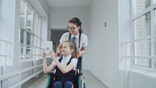 Handheld dolly-like shot of smiling schoolgirl in uniform and glasses pushing wheelchair with laughing handicapped schoolgirl and taking selfies on tablet