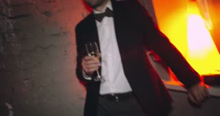 Handheld shot of tipsy stylish man in suit with bowtie standing near brick wall in night club holding flute glass with champagne nodding head to music and winking for camera