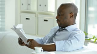 Handsome African-American businessman reading newspaper on coffee break
