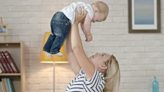 Happy blond laughing woman holding her toddler son in air laughing and talking to him