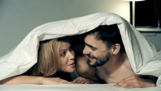 Happy couple lying in bed under duvet, talking and laughing, man kissing his pretty girlfriend on cheek