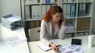 High angle of attractive business woman talking on the phone sitting at the desk with heaps of documents