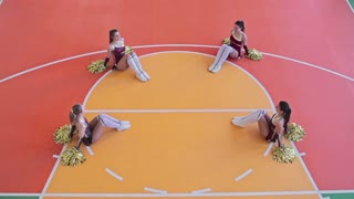 High angle slow motion video of four synchronized cheerleader girls in costumes performing figures lying on floor at practice in school gymnasium