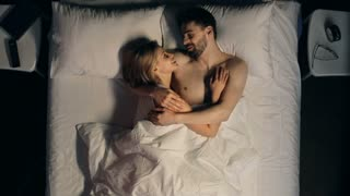 High angle view of charming young couple embracing in bed with white bedding, talking and laughing before sleep