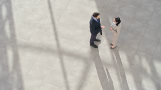 High angle view of young businessman in formalwear with briefcase and Asian businesswoman with digital tablet in hands discussing their project in office lobby, man in suit passing by