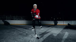 Hockey player ice skating with l-shaped hockey stick pushing