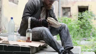Homeless man sitting on a porch of a derelict house having booze and a snack