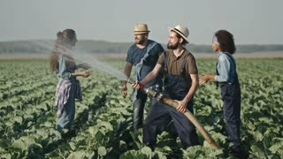 Laughing farmer in overalls holding garden hose and splashing water on screaming female and male friends on cabbage field, then having playful fight as their try to stop him