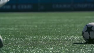 Legs of soccer player running and kicking a ball on green wet grass in slow motion
