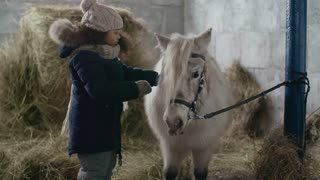 Little African-American girl with curly hair gently hugging pony in barn
