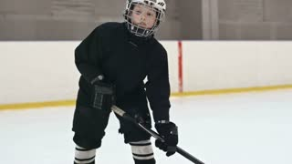 Little boy in black uniform training hockey skills and pushing the puck with stick in slow motion