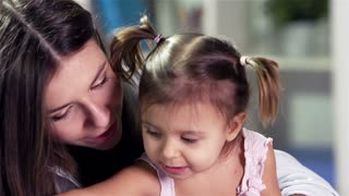 Little cutie painting her mom�s lips with red crayon