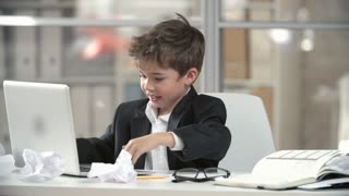 Little dark-haired child in business suit sitting at table behind laptop in office tearing his hair in frustration and laying down on table tiredly.