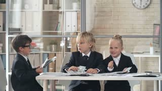 Little girl and two boys in business suit tossing money and laughing in the office