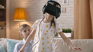 Little girl exploring video game in virtual reality headset while playing with her brother at home