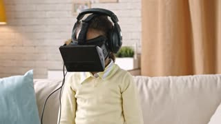Little girl in virtual-reality goggles standing in the living room and turning her head from side to side