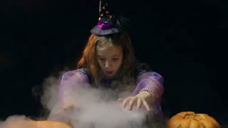 Little girl in witch costume practicing magic over smoky cauldron